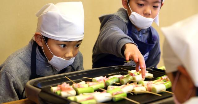 九条ねぎを調理する上鳥羽小学校の児童。ネギの焼け具合を見極めていた=京都市南区、林敏行撮影