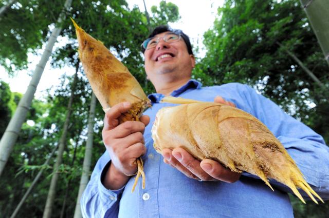 収穫したタケノコを手に、記者の質問に答える小野洋史さん=京都府長岡京市、戸村登撮影
