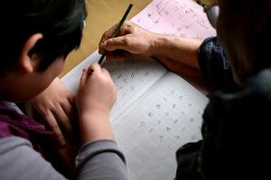 父の字をまねながら、ひらがなの書き取りをする康子さん=兵庫県伊丹市、伊藤進之介撮影