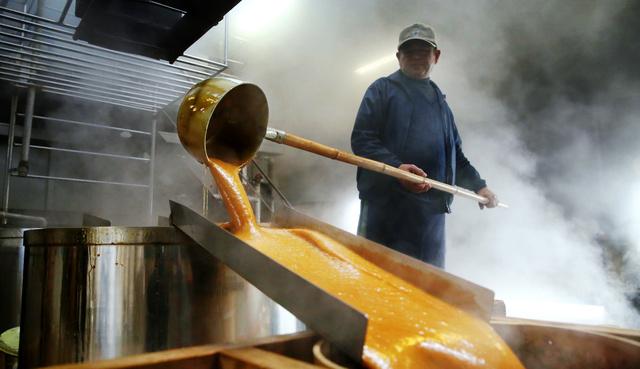 湯気が立ち上る大鍋から、煮詰めて粘度が増した搾り汁をくみ出す。工場の中には、濃厚な甘い香りが漂っていた=徳島県上板町