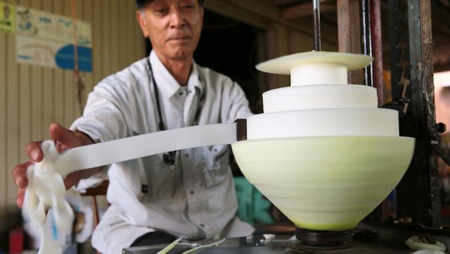 丸いユウガオの実から白いリボンが飛び出す=滋賀県甲賀市