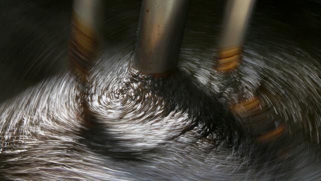 かき混ぜながら釜で炊かれる海苔。炊くほどに増すつやが窓からの光で輝き銀河のような模様を描いた=香川県小豆島町