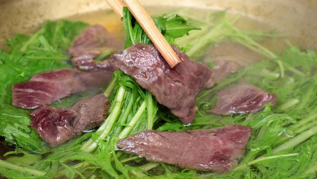 クジラの赤身を熱々のだしにさっとくぐらせる。肉に軽く火が通り、水菜の食感が楽しめる間が食べ頃だ=大阪市中央区
