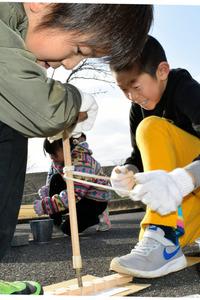 一生懸命にひもを引いて火をおこそうとする児童=近江八幡市江頭町