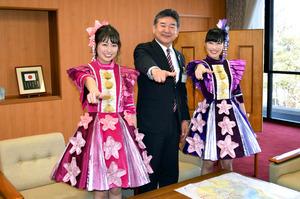 滋賀県東近江市役所を表敬訪問した、ももクロの佐々木彩夏さん(左)、高城れにさんと、決めのポーズをとる小椋正清市長=20日午前、東近江市八日市緑町、
