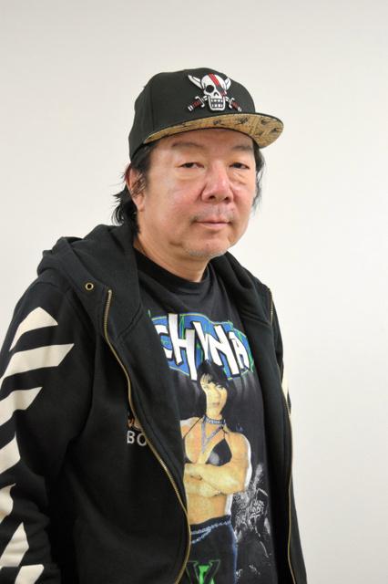 黒いパーカーに黒いキャップを着て立っている古田新太の画像