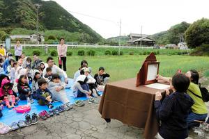 菜の花に囲まれて紙芝居を読んでもらう子どもたち=藤枝市本郷
