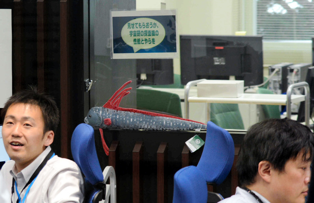 管制室では、「機動戦士ガンダム」のセリフをもじった貼り紙もあった。その下は深海魚「リュウグウノツカイ」のぬいぐるみ=24日、相模原市の宇宙科学研究所
