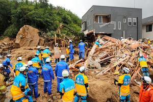 土石流で激しく損壊した住宅周辺で捜索活動をする警察官ら=2018年7月8日午後0時4分、広島県熊野町川角5丁目、