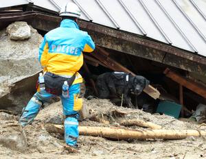 土石流で激しく損壊した住宅周辺で捜索活動をする警察官ら=2018年7月8日午後0時4分、広島県熊野町川角5丁目、細川卓撮影