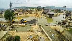 堤防が決壊し、甚大な浸水被害をもたらした小田川の支流・末政川(右下から奥中央)。ようやく重機による作業がはじまったが、道路は水浸しになったままだ=12日