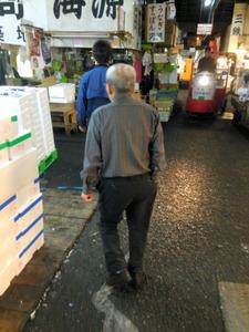卸売場に向かう仲卸「て良」の井上武久さん。尻ポケットに右手を突っ込んで歩くのが癖だ=東京都中央区の築地市場