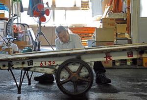 店先で小車の車輪を修理する「桐生製車」の桐生源三さん=2018年8月10日、東京都中央区の築地市場、樫山晃生撮影