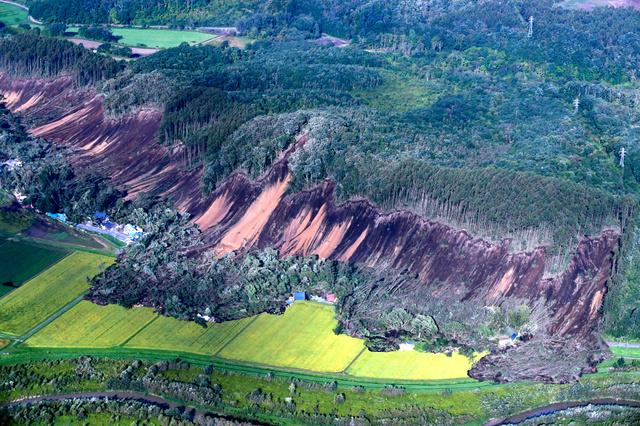地震で山肌が崩れ住宅が土砂に巻き込まれていた=2018年9月6日午前7時18分、北海道厚真町、朝日新聞社機から、山本壮一郎撮影