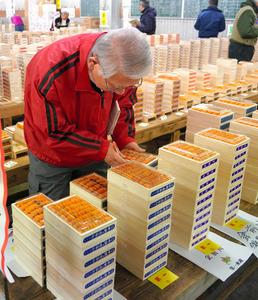 世界中のウニが積み上げられた低温卸売場で、仲卸たちが品定めをしていく=樫山晃生撮影