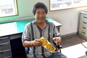 漁師の山本直嗣さん。手にしているのが、これから語られる「ステッカー」=愛知県南知多町の豊浜漁協