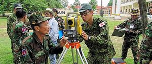 カンボジア陸軍の工兵部隊に測量技術を指導する隊員たち=いずれも6月、カンボジア・コンポンスプー州、陸自提供