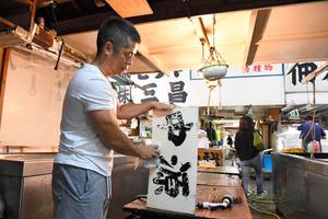 妻の両親が経営していた仲卸「中源」の看板を下ろす保坂順也さん。普段は別の仕事をしているが、豊洲に移らず築地で廃業するため、片付けの手伝いに訪れた。「おつかれさま、という気持ちで看板を下ろしました」と話した=2018年10月6日午後、東京都中央区の築地市場、諫山卓弥撮影