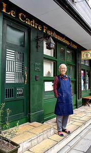 元店舗の前に立つ浅尾空人さん。金色で書かれた「Le Cadre」は仏語で額縁という意味