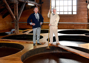 直径約2メートル、高さ2・5メートルの木桶が並ぶ蔵に立つ柴沼さん(左)と職人の鈴木孝平さん(右)