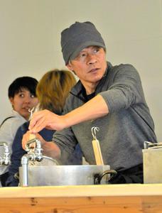 調理をしながら来店者に目配りをする小山洋明さん=2019年3月29日、北九州市若松区