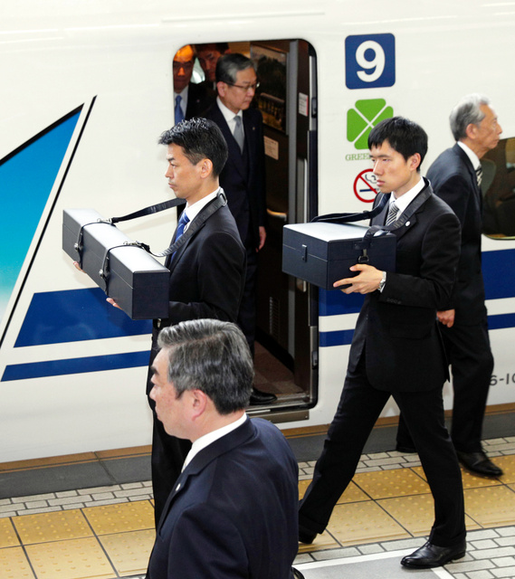 天皇、皇后両陛下に随行し、「三種の神器」の剣と璽をそれぞれ入れたケースを携えJR名古屋駅に到着した侍従=17日午後3時、代表撮影