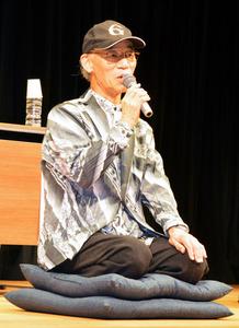 「富野由悠季の世界」オープニング記念トーク冒頭、幕が開くと舞台中央で座布団に座った富野さんがお客さんをお迎え=6月22日、福岡市の福岡市美術館