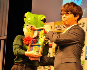 カエルのかぶりもので「マンガ大賞2020」授賞式に登壇した「ブルーピリオド」作者・山口つばささん(左)と、プレゼンターの篠原健太さん=3月16日、東京・有楽町