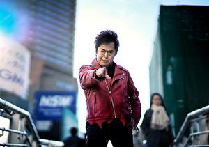 右手の人さし指を突き出すのは決めのポーズだ。トレードマークの赤いマフラーこそ首に巻いていないものの、熱い魂を込めて「ゼーット!」=東京都内、村上健撮影