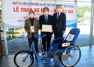 岩本功理事長(左)に支援金を贈った風井啓二会長(中央)と川元正幹事。手前がベトナム製の特殊車いす=2020年5月13日午後2時15分、山口県下松市