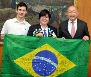 寄せ書き入りのブラジル国旗を持つ宮原識水音さん(中央)と、鳥栖高の制服を着たブルーノ・ド・カルモさん(左)=2020年6月3日午後2時29分、佐賀県鳥栖市役所