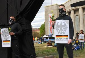 ドイツ連邦共和国のための基本法(憲法)と書かれたポスターを掲げ、新型コロナウイルス対策で政府が導入した様々な規制に反対する人たち=2020年4月25日、ベルリン、野島淳撮影
