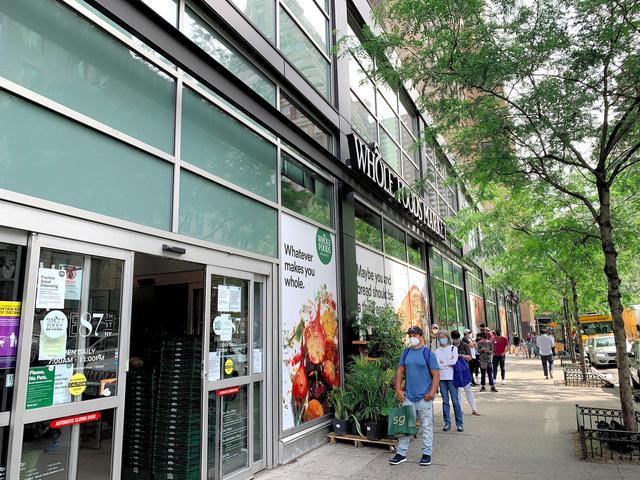 アマゾン傘下のスーパー「ホールフーズ・マーケット」。入店人数が制限され、買い物客は外に列をつくっていた=6月、米ニューヨーク、江渕崇撮影
