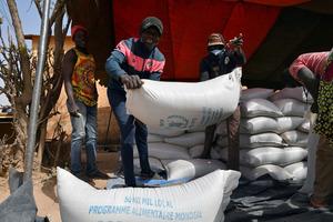 ブルキナファソのピシラで1月24日、WFPからの食料を運ぶ人たち=ロイター