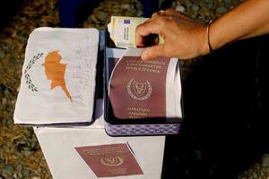 キプロスの首都ニコシアで14日、国会議員の汚職に抗議する人が作ったパスポートの模造品=AP