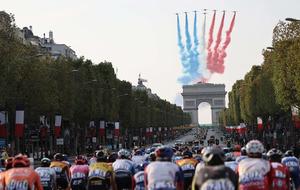 9月20日、航空機によって上空に赤、白、青色の直線が描かれるなか、パリのシャンゼリゼ通りを走る選手たち=AFP時事
