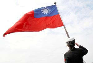 2018年1月、台湾の「青天白日満地紅旗」に向かって敬礼する台湾軍の兵士=AP。中国側は、この旗を掲げた台湾側の行為が「一つの中国」原則に反すると非難した