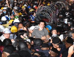 バリケードを壊して警官隊ともみ合うデモ参加者たち=2020年10月21日午後、バンコク、乗京真知撮影