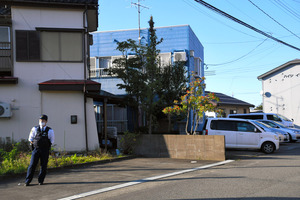 現場のアパート(左から2軒目)の近くでは警察官が立っていた=2020年10月20日午後3時16分、新潟県柏崎市、小川聡仁撮影