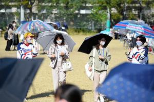 秋晴れのもと、傘を差して新入生の勧誘が行われた=2020年10月25日午後1時36分、長崎市文教町、横山輝撮影