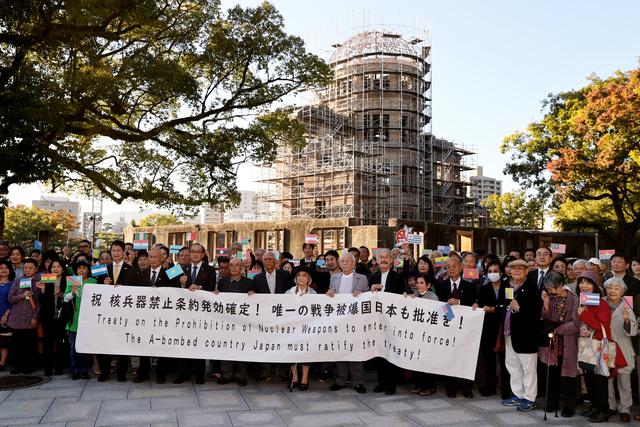 原爆ドーム前で日本の条約批准を求める横断幕を掲げる広島の被爆者7団体のメンバーら=2020年10月25日午後3時49分、広島市中区、上田潤撮影