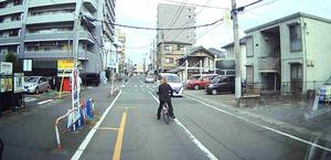 対向車線側に自転車を寄せる成島明彦容疑者。この行為が逮捕容疑となった(目撃者の男性提供のドライブレコーダーから)