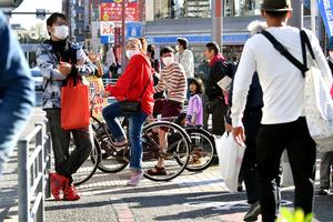信号待ちの間、大阪都構想の街頭演説を遠巻きに見る人たち=2020年10月25日午後、大阪市平野区、井手さゆり撮影