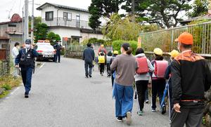 クマの出没のため、小学生の登校時には警察官や日光市職員らが警戒した=2020年10月16日午前7時35分、栃木県日光市今市