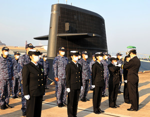 阿部純一艦長(右端)から潜水艦乗員の証しの「ドルフィンマーク」を授与される海上自衛隊の女性隊員=2020年10月29日午前8時4分、広島県呉市、上田潤撮影