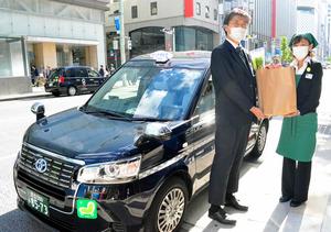 松屋銀座の新サービスでは、買い物を社員が代行し、商品をタクシーの運転手に託す=松屋提供