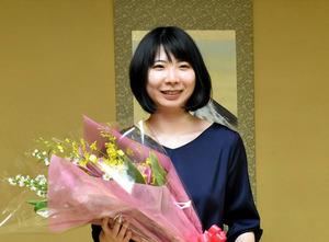 初防衛を果たし、花束を手に笑顔を見せる西山朋佳女流王将=2020年10月30日、東京都渋谷区、村瀬信也撮影