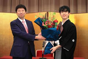 就位式で師匠の杉本昌隆八段(左)から花束を受け取る藤井聡太王位=2020年11月12日午後6時39分、東京都千代田区、長島一浩撮影