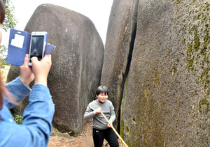 「鬼の一刀岩」の前では木の枝などを手に記念撮影する親子連れが相次いでいた=2020年11月22日、岐阜県瑞浪市・御嵩町にまたがる鬼岩公園、戸村登撮影