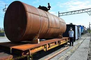 軽貨車の上に仮置きにされているタンク。表面は塗装がはげて、さびた状態。溶接技術が普及する前の製造とあって、鋼板を接合するためリベットが打ち込まれている。後ろは1900年製の貨車=2020年11月12日午前11時20分、三重県いなべ市大安町、臼井昭仁撮影